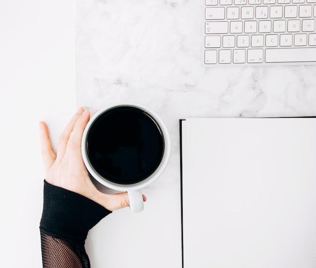 Nahaufnahme der hand einer person, die schwarze kaffeetasse mit tagebuch und tastatur auf schreibtisch hält