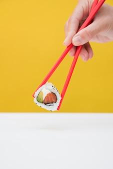 Nahaufnahme der hand einer person, die sushirolle mit roten essstäbchen gegen gelben hintergrund hält