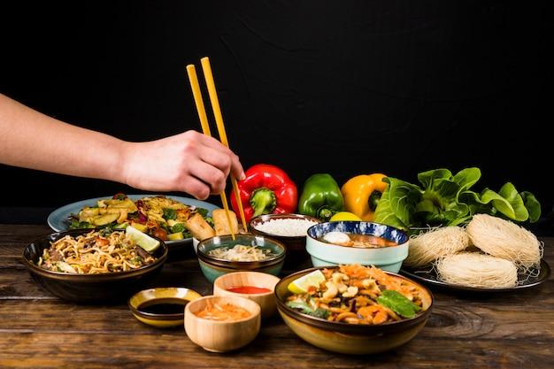 Nahaufnahme der hand einer person, die thailändisches lebensmittel mit essstäbchen auf tabelle gegen schwarzen hintergrund isst