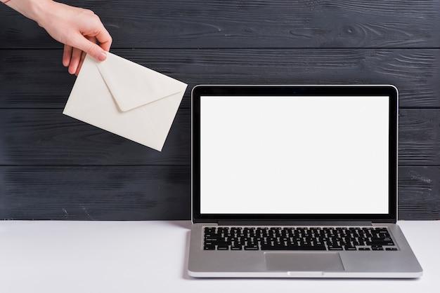 Nahaufnahme der hand einer person, die weißen umschlag nahe dem laptop auf schreibtisch gegen schwarzen hölzernen hintergrund hält