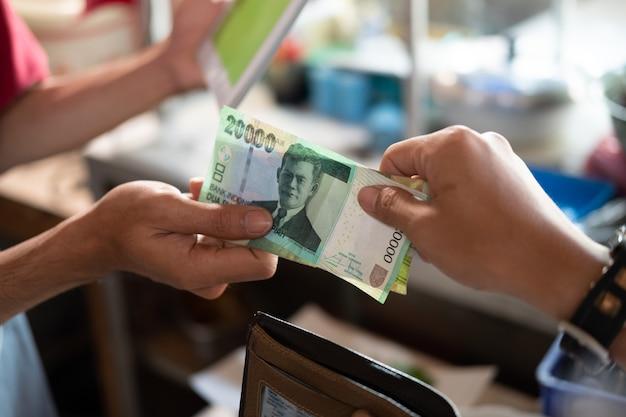 Nahaufnahme der hand eines asiatischen käufers, der in rupiah zu einem lebensmittelstandverkäufer zahlt, nachdem er an einem lebensmittelstand gegessen hat