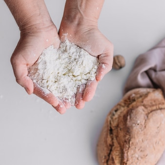 Nahaufnahme der hand eines bäckers, die mehl hält