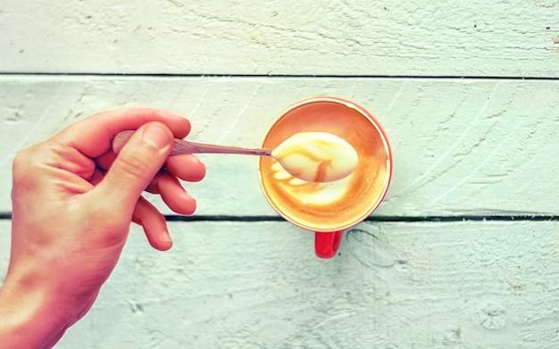 Nahaufnahme der hand eines barista hebt einen schaum mit frischem cappuccino in einer roten tasse auf einem weißen alten holztisch. ansicht von oben Premium Fotos