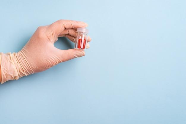Nahaufnahme der hand eines doktors, die pillen in der flasche hält