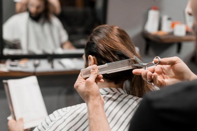 Nahaufnahme der hand eines friseurs, welche das haar des männlichen kunden mit scheren schneidet