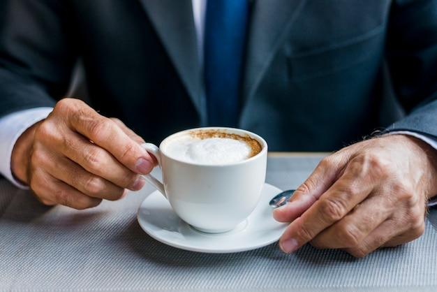 Nahaufnahme der hand eines geschäftsmannes, die tasse kaffee hält