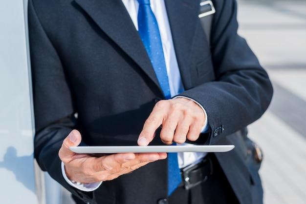 Nahaufnahme der hand eines geschäftsmannes unter verwendung der digitalen tablette