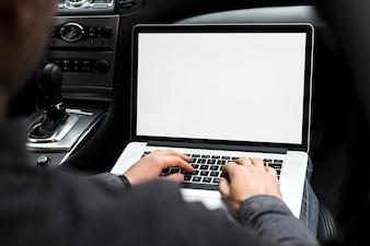 Nahaufnahme der Hand eines Geschäftsmannes unter Verwendung des Laptops, der im Auto sitzt