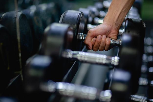 Nahaufnahme der hand eines jungen mannes, der eine hantel hält, nachdem er eine in der reihe für das training im fitnessstudio ausgewählt hat,