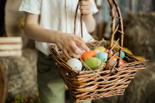 Nahaufnahme der hand eines kindes, die bunte eier in einem weidenkorb heraussucht. osterferien