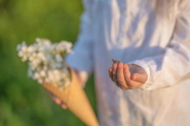 Nahaufnahme der hand eines kindes mit marienkäfer, der darüber kriecht und kurz davor ist, abzuheben.