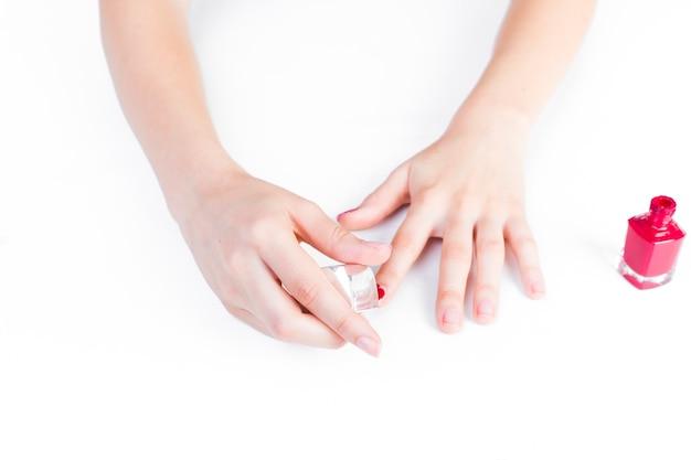 Nahaufnahme der hand eines mädchens, die roten nagellack anwendet