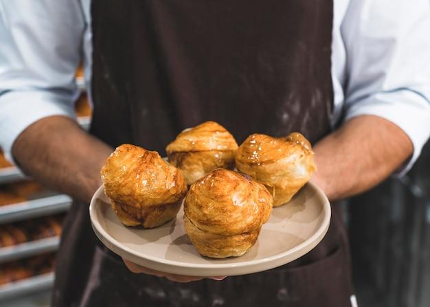 Nahaufnahme der hand eines männlichen bäckers, die süßen blätterteig auf platte hält