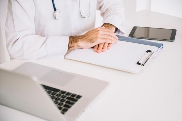 Nahaufnahme der hand eines männlichen doktors auf klemmbrett mit laptop auf schreibtisch