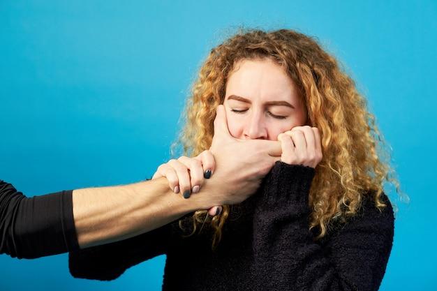 Nahaufnahme der hand eines mannes, die den mund eines attraktiven mädchens oder einer attraktiven jungen rothaarigen frau bedeckt. konzept von häuslicher gewalt, sklaverei, grausamkeit.