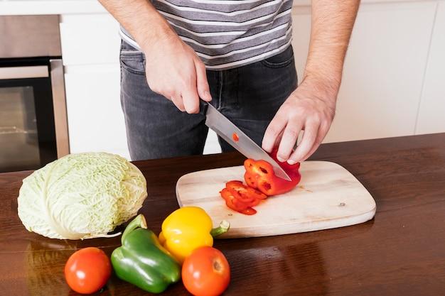 Nahaufnahme der hand eines mannes, die den roten bellpepper mit scharfem messer auf hackendem brett schneidet