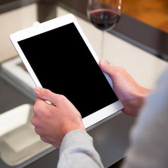 Nahaufnahme der hand eines mannes, die digitale tablette mit leerer anzeige hält