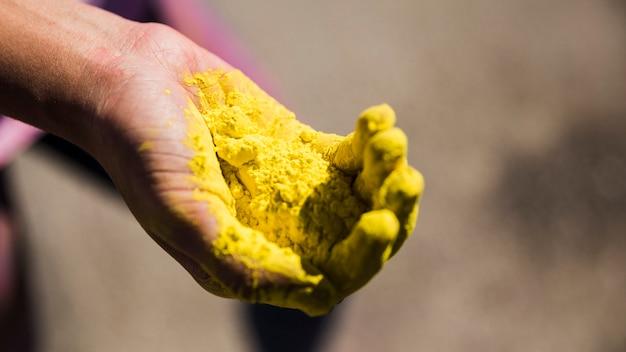 Nahaufnahme der hand eines mannes, die gelbe holi farbe anhält