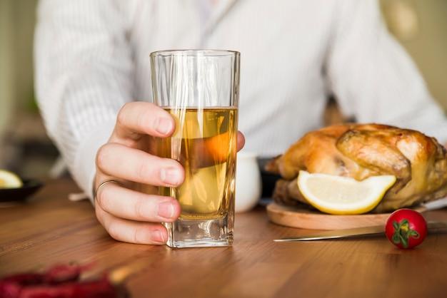 Nahaufnahme der hand eines mannes, die glas eines bieres mit ganzem gebratenem huhn auf tabelle hält