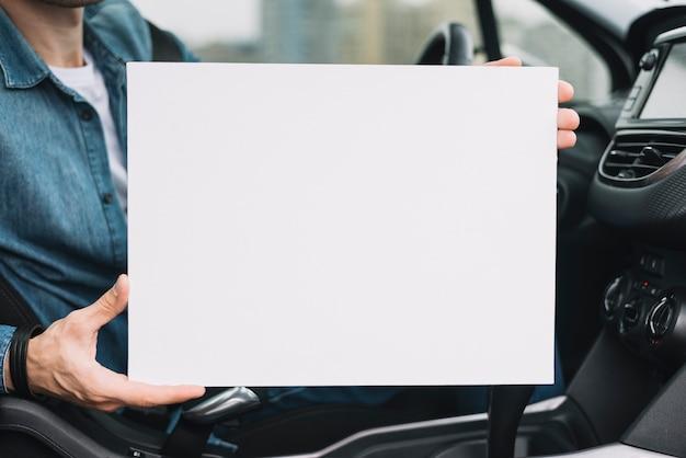 Nahaufnahme der hand eines mannes, die leeres weißes plakat zeigt