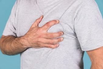 Nahaufnahme der Hand eines Mannes, die sein Herz in den Schmerz hält