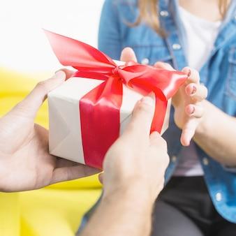 Nahaufnahme der hand eines mannes, die seiner frau geschenk gibt