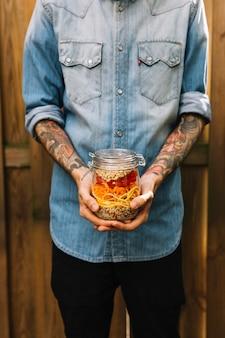 Nahaufnahme der hand eines mannes, die teigwarensalat im weckglas hält
