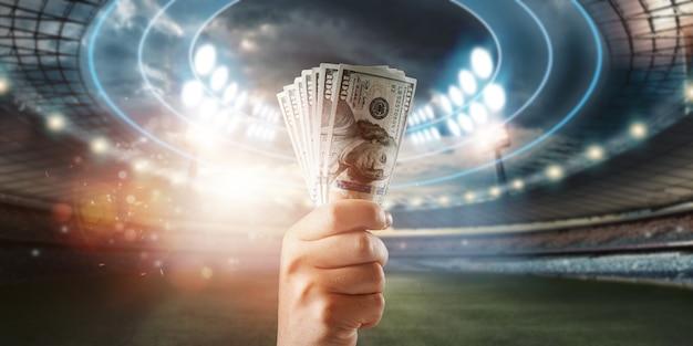 Nahaufnahme der hand eines mannes, die us-dollar vor dem hintergrund des stadions hält. das konzept des sportwettens, des gewinns aus wetten und glücksspielen. american football.