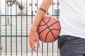 Nahaufnahme der Hand eines Mannes mit Basketball vor Zaun