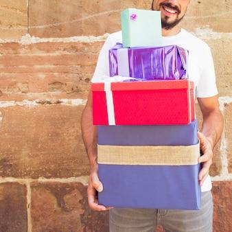 Nahaufnahme der hand eines mannes mit gestapelten geschenken