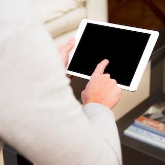 Nahaufnahme der Hand eines Mannes, welche die digitale Tablette mit dem Finger berührt