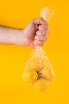 Nahaufnahme der hand eines mannes, welche die reifen zitronen im netz gegen gelben hintergrund hält