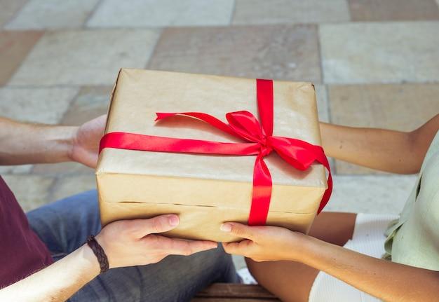 Nahaufnahme der hand eines paares, die geschenk hält