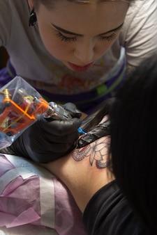 Nahaufnahme der hand eines tätowierungsmeisters in den schwarzen handschuhen mit einer tätowierungsmaschine macht eine tätowierung entsprechend der skizze