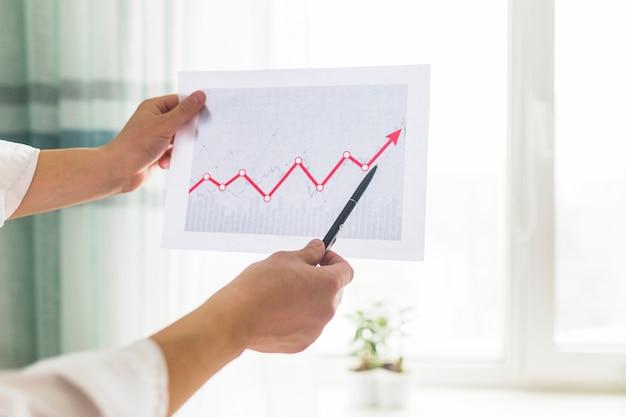 Nahaufnahme der hand eines wirtschaftlers, die diagramm am arbeitsplatz analysiert