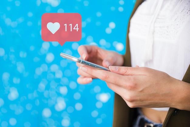 Nahaufnahme der hand halten mobile mit wie benachrichtigungsikone gegen glänzenden blauen hintergrund