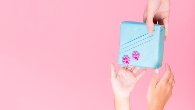 Nahaufnahme der hand holding wickelte geschenkbox über rosa hintergrund ein