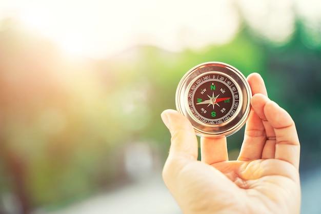 Nahaufnahme der hand kompass mit unscharfer grüner natur und sonnenlicht mit aufflackernhintergrund halten.