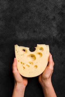 Nahaufnahme der hand maasdam-käse gegen schwarzen strukturierten hintergrund halten