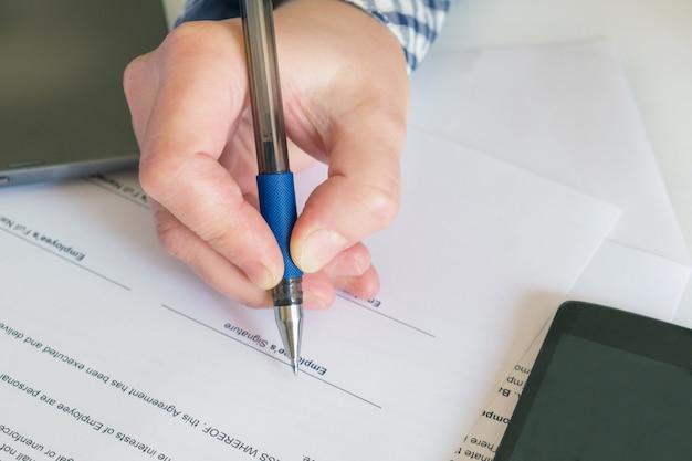 Nahaufnahme der hand mit einem stift auf dem hintergrund von offiziellen papierdokumenten. unterzeichnung des arbeitsvertrages.