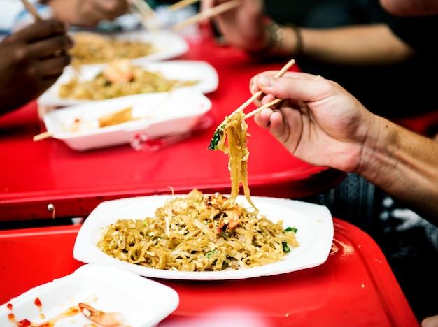 Nahaufnahme der hand mit essstäbchen und thailändischem lebensmittel der auflage