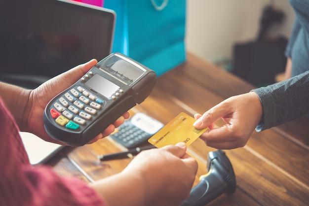 Nahaufnahme der hand mit kreditkarte zum bezahlen, indem sie die kreditkarte an das personal am kreditkarten-swipe-automaten senden. onlinebezahlung