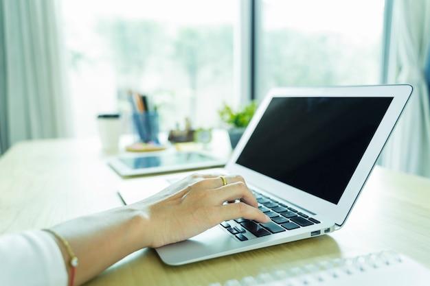 Nahaufnahme der hand mit laptop mit schwarzem bildschirm auf tisch im büro. technologie- und geschäftskonzept.