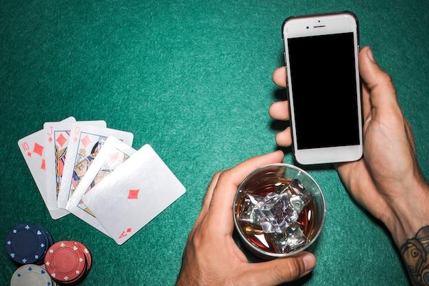 Nahaufnahme der hand mobiltelefon- und whiskyglas über der pokertabelle halten
