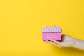 Nahaufnahme der Hand rosa Kasten gegen gelben Hintergrund halten