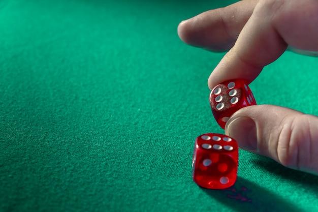 Nahaufnahme der hand rote würfel mit einer gewinnenden kombination auf grünem stoff in einem kasino halten.