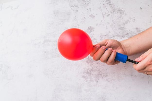 Nahaufnahme der hand roten ballon mit pumpe gegen wand durchbrennend