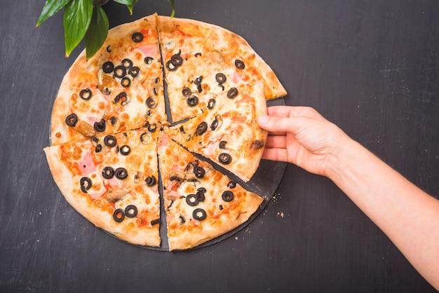 Nahaufnahme der hand scheibe der pizza auf dunklem hintergrund halten