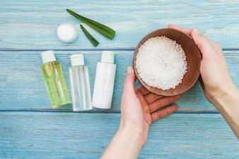 Nahaufnahme der Hand Schüssel Steinsalze mit aloevera Sprühflaschen und Sahne halten