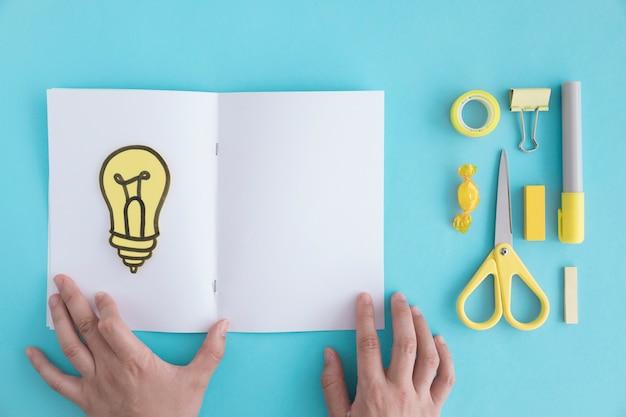 Nahaufnahme der hand seite mit glühlampe und briefpapier auf blauem hintergrund halten